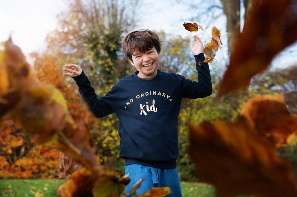 girl-laughing-autumn-leaves-different-kids-clothes